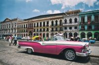pink-cadillac-cuba-blue-sky-warm-day-main-street-people-clouds.