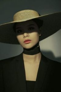 woman in black suit and brown hat