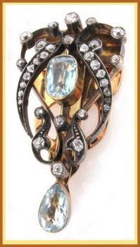 gold clip brooch, mounted with two aquamarines and graduated circular cut diamonds
