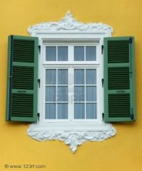 arabesque window frame with open green shutter yellow wall