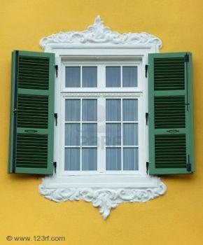 arabesque window frame with open green shutter yellow wall