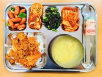 Korean School Lunch of Spicy Stir Fried Pork, Rice Cake Soup, and Various Banchan