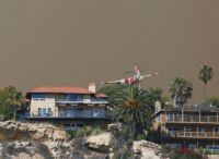 Fire fighters fly over Laguna Beach CA