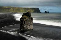 Basalt sea stack on a black sand beach in Iceland