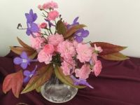 A small bowl of tiny pink fairy roses,blue geraniums and nandina leaves