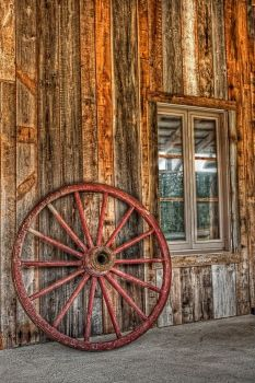 Vintage wagon wheel by wooden wall