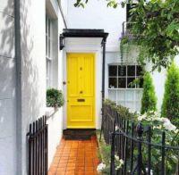 Door of lemon yellow with walkway and rod iron fence