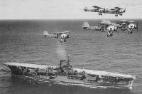HMS Ark Royal with flight of Fairey Swordfish torpedo planes overhead