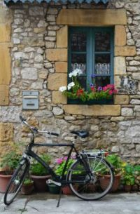 A bicycle outside a medieval village house in the Dordogne region of France by Colin Bedson