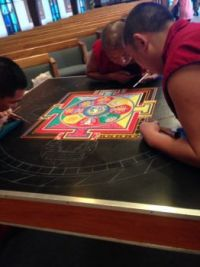 Exiled Tibetan monks with sand mandala in progress