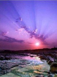 Purple sunset and rocky seascape