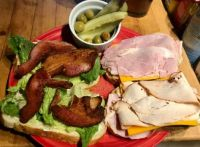 Ham, turkey and bacon sandwiches on Italian bread with sharp cheddar, romaine, olive oil mayo and black pepper, plus a side of dill pickles and pimiento olives