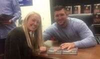 Granddaughter getting Tim Tebow's autograph.
