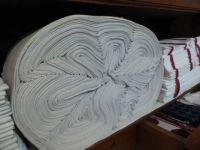 A nearer view of a roll of linen in a linen cupboard.