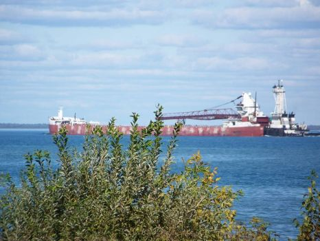 Tugboat pushing freighter on Lake Huron