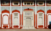 White Door with Carvings on Red Building