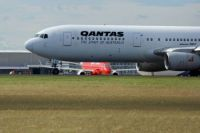 Qantas 767 about to leave Tullamarine Airport. A Virgin Embraer in background.