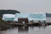 Fishing Stage dwarfed by massive Iceberg.