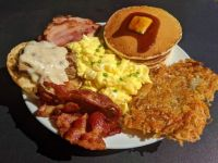 Grand Slam style breakfast - Buttermilk pancakes, eggs, hash brown, bacon, ham, biscuit, sausage links, and gravy