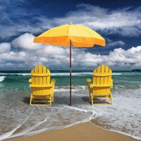 Beach surf with yellow chairs and umbrella