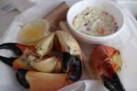 Stone Crab Claws with a side of coleslaw, a mallet, and warm butter for dipping