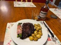 Flame grilled Ribeye with bacon-wrapped asparagus and seasoned potatoes paired with bourbon