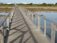 Pathway above little salt lakes towards Le Saline beach, Stintino, Sardinia, Italy