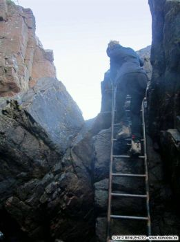 """The Shrine"" - Pia-Maria on her way down to a very deep crevice. Bornholm."