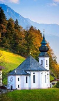 A traditional onion dome Roman Catholic church by Watzmann mountains at Berchtesgaden in Bavaria, Germany