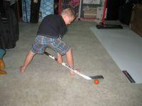 Grandson practising hockey shot.