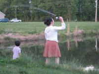Mama teaches son how to fish.