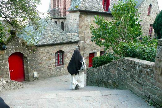 Nun with backpack.  Mont St-Michel, France