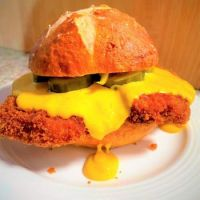 Home Made Pork Schnitzel with Red Curry Cheese Sauce and Pickles on a Pretzel Bun