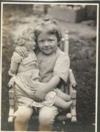 Vintage  Photo of A Smiling Child Holding Her Beloved Doll