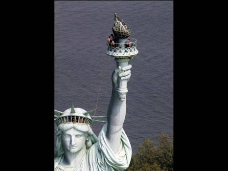 The Statue of Liberty - Workers getting ready to remove the glass-paned flame from the torch