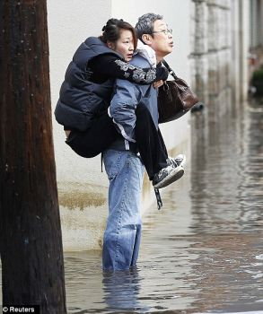 "Husband carries his wife through the water in the aftermath of ""Sandy"""