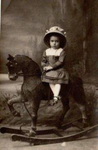 Victorian Child sitting (Side-Saddle) On A Rocking Horse