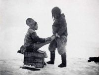An Inuit man in Greenland warms up his wife's feet, 1890s