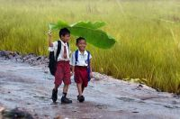 two-kids-under-a-banana-leaf-in-the-rain-indonesia