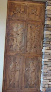 CARVED DOORS ON EACH SIDE OF A FIRE PLACE