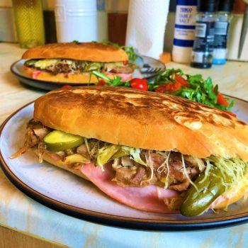 Cubanos on homemade rolls, with crispy pork carnitas, homemade garlic dill pickles, honey ham, and Gruyère cheese
