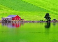 Barn at the lake and rolling green hills