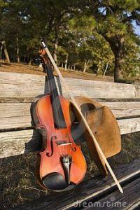 chapéu-do-violino-e-de-cowboy-em-um-banco-de-parque-5435628