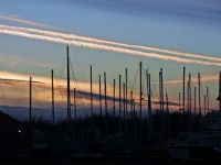 Contrails at the marina at sunset