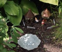 Two little gnome neighbours having a chat under the hostas