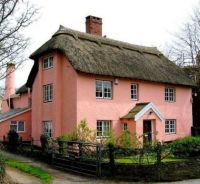 pink cottage with thatched roof