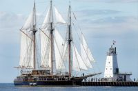 The tall ship Peacemaker passes the Ludington Lighthouse