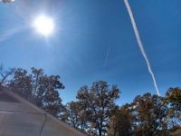 THE SUN, AIRPLANE, AND A CONTRAIL