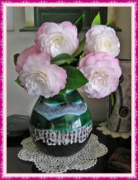 Vase of pale pink camellias.