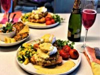 Eggs Benedict with brown butter hollandaise, smoked salmon, crab cakes and mango salad